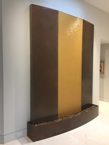 Image of a bronze waterwall with a glass inset.
